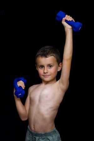 Low key portrait of a kid doing fitness photo