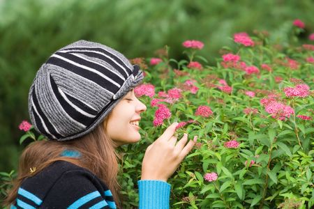 Beautiful woman with hat smelling purple flowers in a garden photo