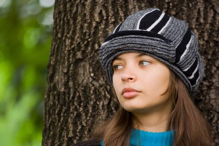 Close up portrait of a beautiful woman with hat standing near an old tree photo