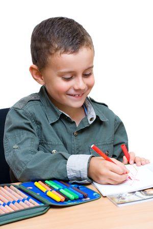 Portrait of a cute schoolboy drawing photo