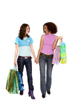 Two young women with bags shopping for Christmas, isolated on white photo