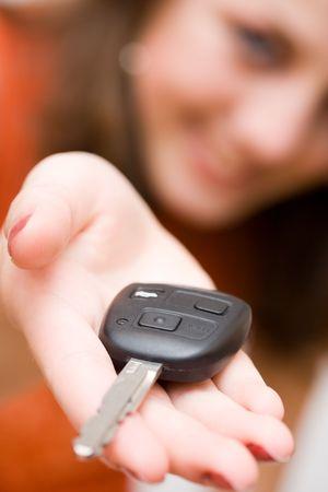 Young sales woman offering car keys Stock Photo