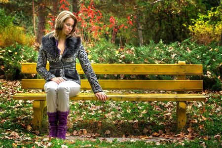 Beautiful blonde woman sitting on a bench in park Stock Photo