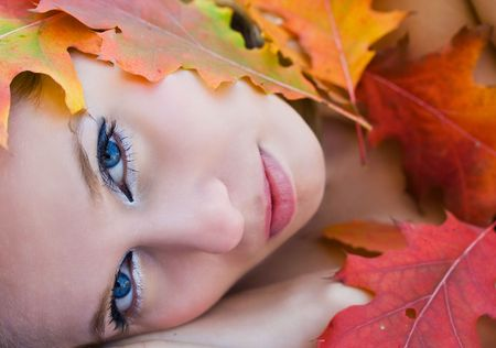 Close up portrait of a beautiful woman covered with colorful leaves Stock Photo