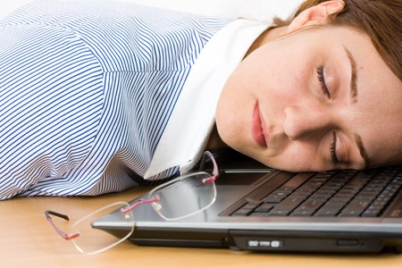 Tired businesswoman sleeping on a laptop keyboard photo