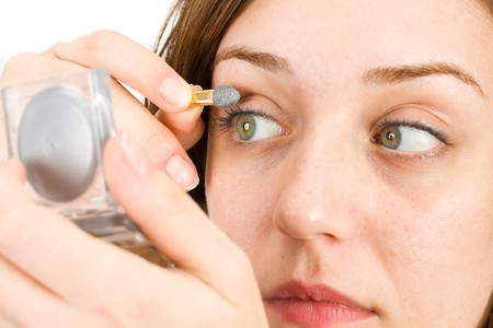 Portrait of a young woman doing makeup photo