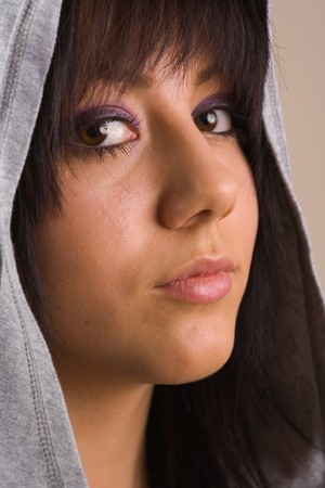 Portrait of a beautiful young brunette with sweater and hood photo