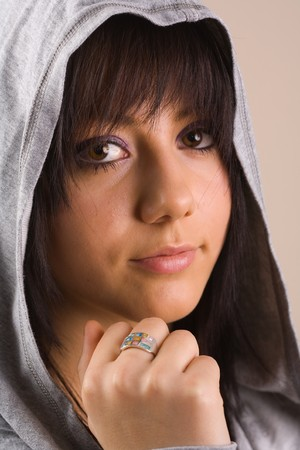 Portrait of a beautiful pensive teenager with sweater and hood photo