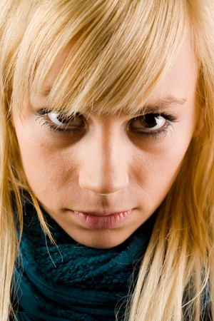 Intense look of a blonde girl with a blue scarf wrapped around her neck photo