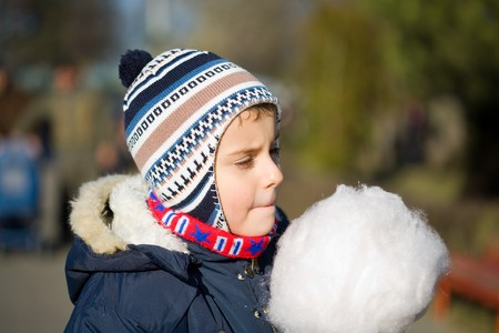 outdoor eating: Portrait of a cute kid outdoor eating cotton candy Stock Photo