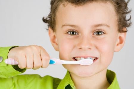 brush teeth: Beautiful boy brushing teeth, isolated on white Stock Photo