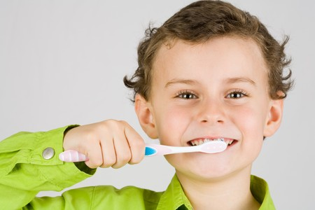 Beautiful boy brushing teeth, isolated on white Stock Photo
