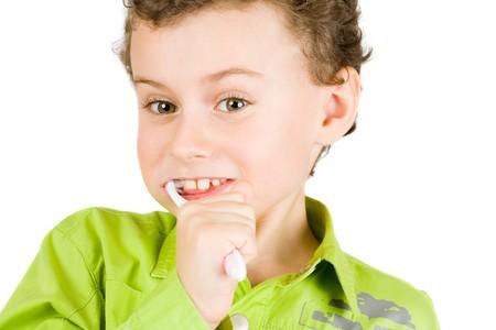 Beautiful boy brushing teeth, isolated on white photo