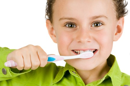 Beautiful boy brushing teeth, isolated on white Reklamní fotografie