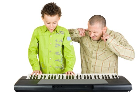 badly: Schoolboy playing badly at the piano while the teacher shows disappointment Stock Photo