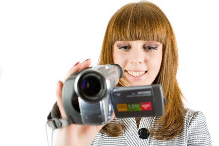 Girl using video camera (camcorder), isolated on white background photo