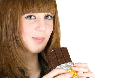 Pretty blonde eating chocolate, isolated on white background photo
