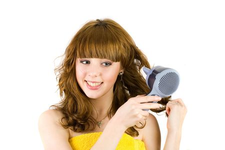 Young woman wrapped in yellow towel using hair drier, isolated on white background photo