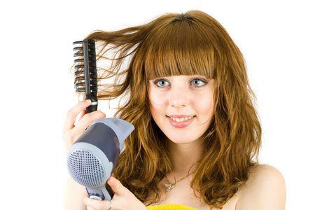Young blonde woman  wrapped in yellow towel, using hair drier photo