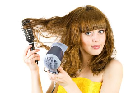Young blonde woman  wrapped in yellow towel, using hair drier Stock Photo - 4272431
