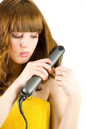 straightener: Blonde girl using a hair straightener