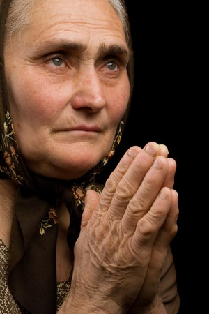 Close up portrait of an old woman praying photo