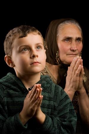 praying together: Grandmother and grandson praying together
