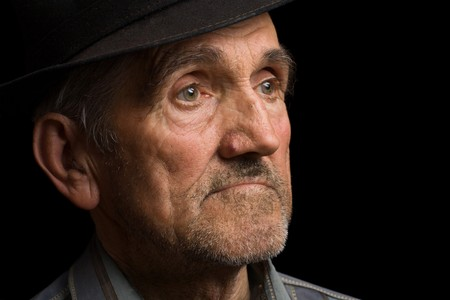 aging american: Portrait of an old man with hat, isolated on black