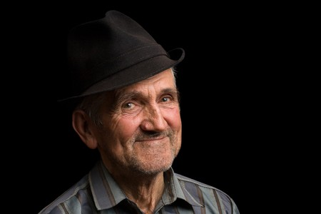Portrait of a happy old man with hat, isolated on black