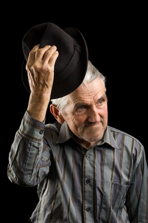 aging american: Old man saluting with hat, isolated on black Stock Photo