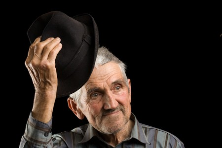 aging american: Old man saluting with his hat, isolated on black Stock Photo