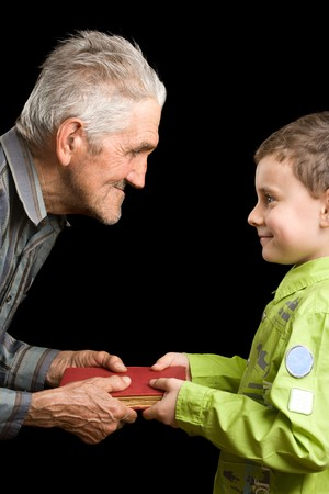 Grandfather giving a book to his grandson Stock Photo - 4370875