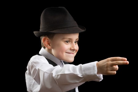 Portrait of a gorgeous little boy posing as a gangster, isolated on black photo