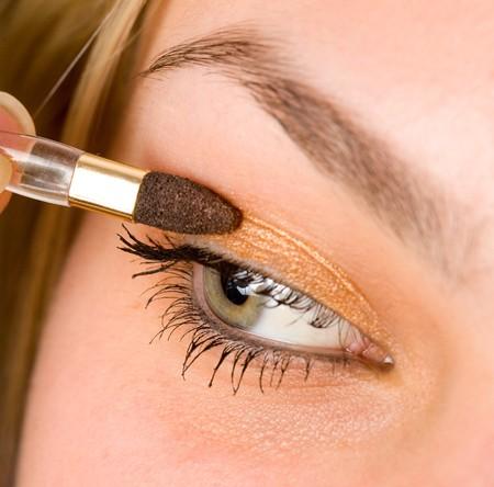 Closeup portrait of a beautiful woman applying makeup photo