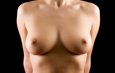 girl boobs: Anonymous perfect natural breasts isolated over black background Stock Photo