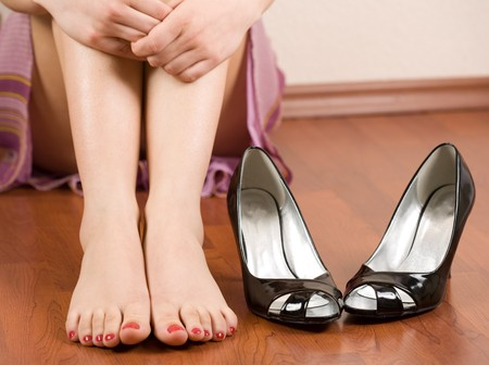 female feet: Woman feet with shoes nearby
