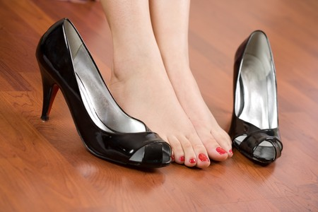 foot pain: Woman feet with shoes nearby