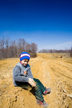 8 year old boy playing with mud in a deserted landscape photo