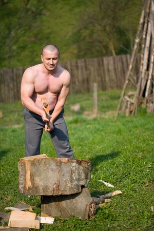 skilled: Strong man splitting wood with an axe in the countryside Stock Photo