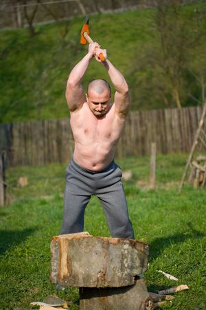 Strong man splitting wood with an axe in the countryside Stock Photo - 4761235