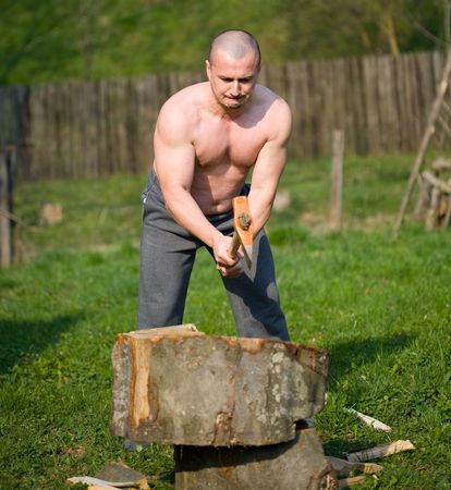Strong man splitting wood with an axe in the countryside Stock Photo - 4761232