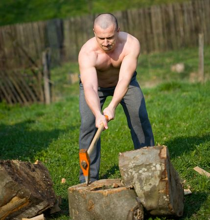 Strong man splitting wood with an axe in the countryside Stock Photo - 4761234