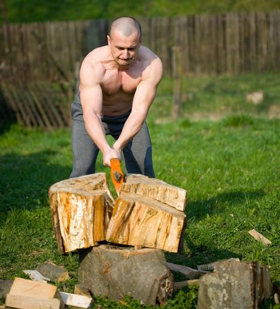 Strong man splitting wood with an axe in the countryside Stock Photo - 4761221