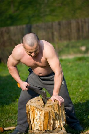 Strong man splitting wood with an axe in the countryside Stock Photo - 4761229