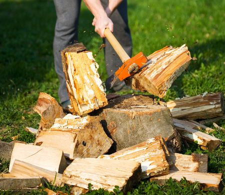 Hands of a strong man splitting wood with an axe, focus is on the axe, motion freezing in the moment it split Stock Photo - 4761230