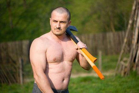 Strong man splitting wood with an axe in the countryside Stock Photo - 4761231