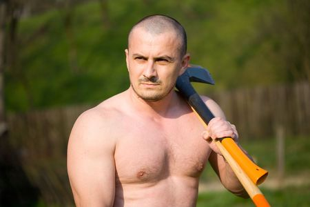 Strong man splitting wood with an axe in the countryside Stock Photo - 4761223