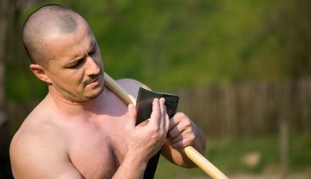 Strong man splitting wood with an axe in the countryside Stock Photo - 4761224