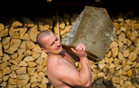 Strong man lifting a huge log, outdoor scene Stock Photo - 4761214