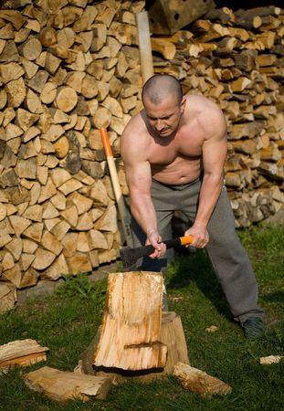 hombre fuerte: Hombre fuerte divisi�n de madera con un hacha en el campo